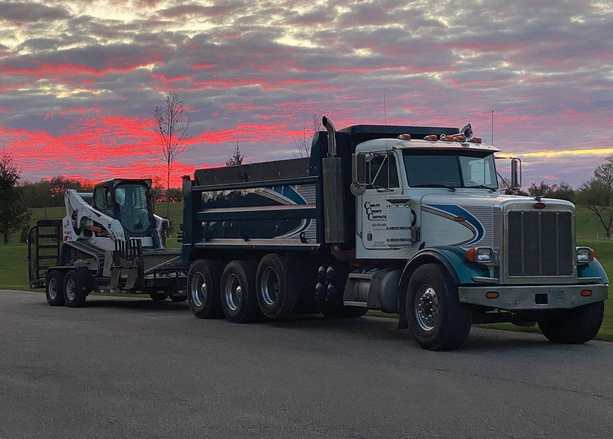 complete concrete construction dumptruck and bobcat fleet with sunset