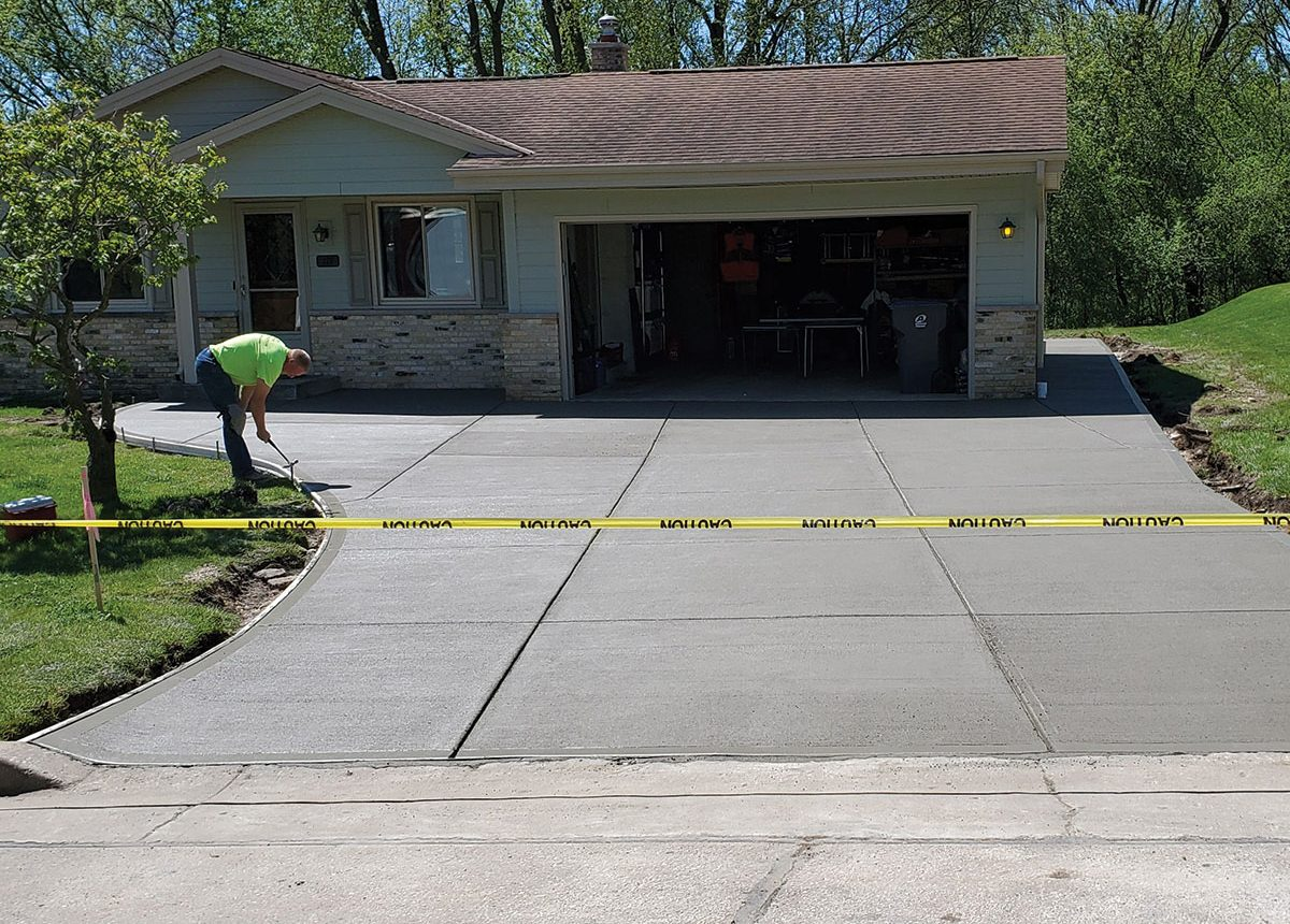 complete new construction finishing a new driveway in a residential neighborhood