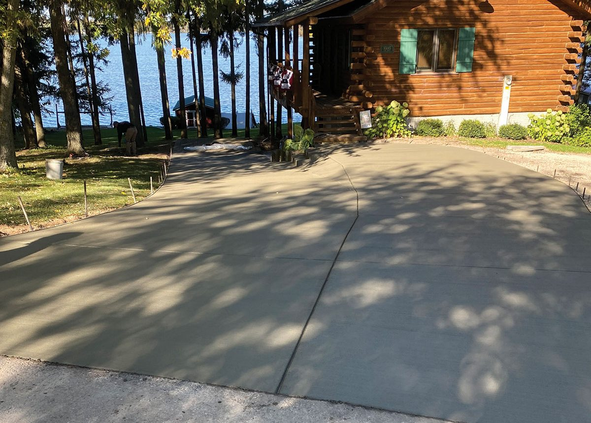 new paved concrete driveway for log cabin on lake