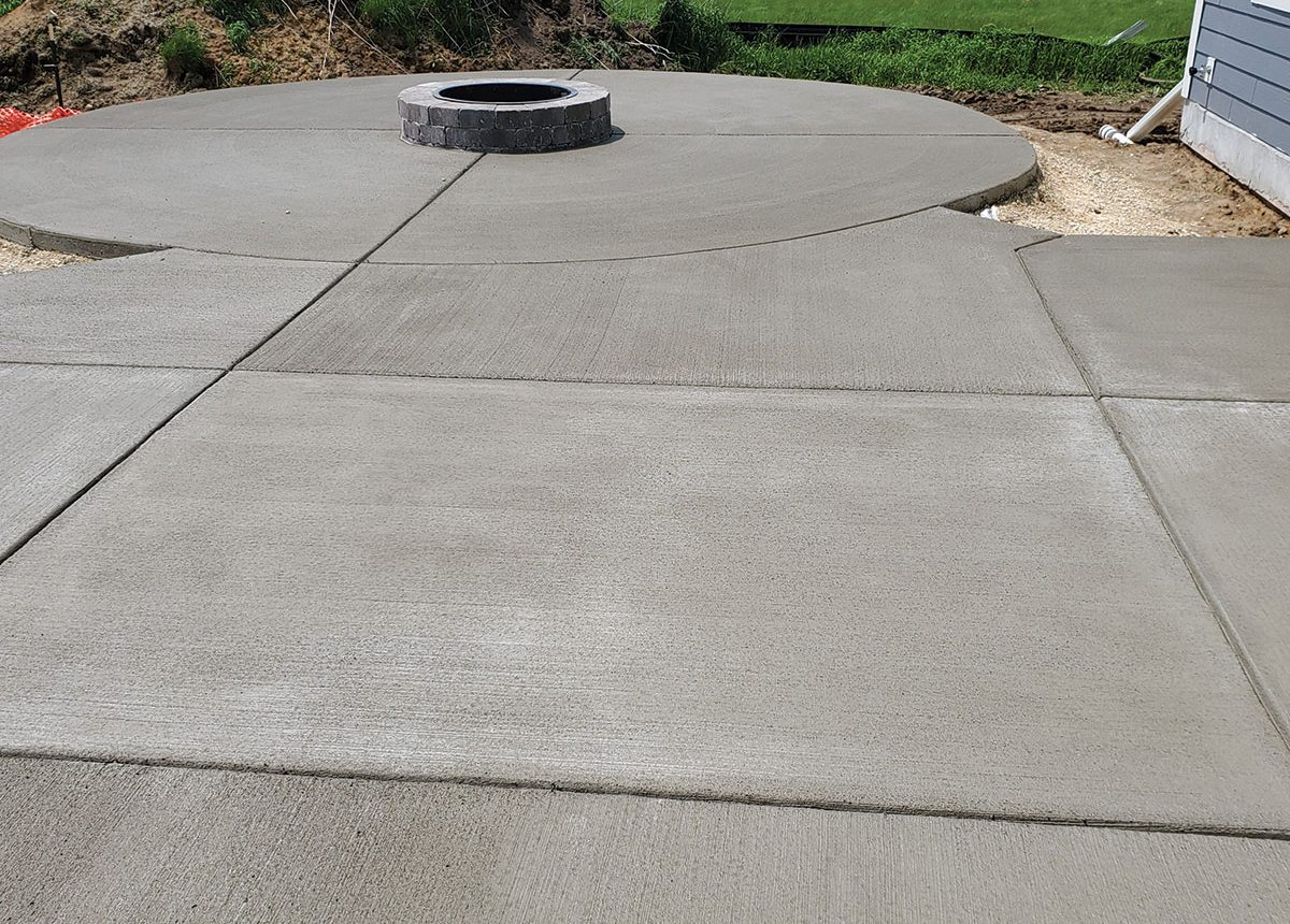 residential concrete paved patio with hardscape fire pit